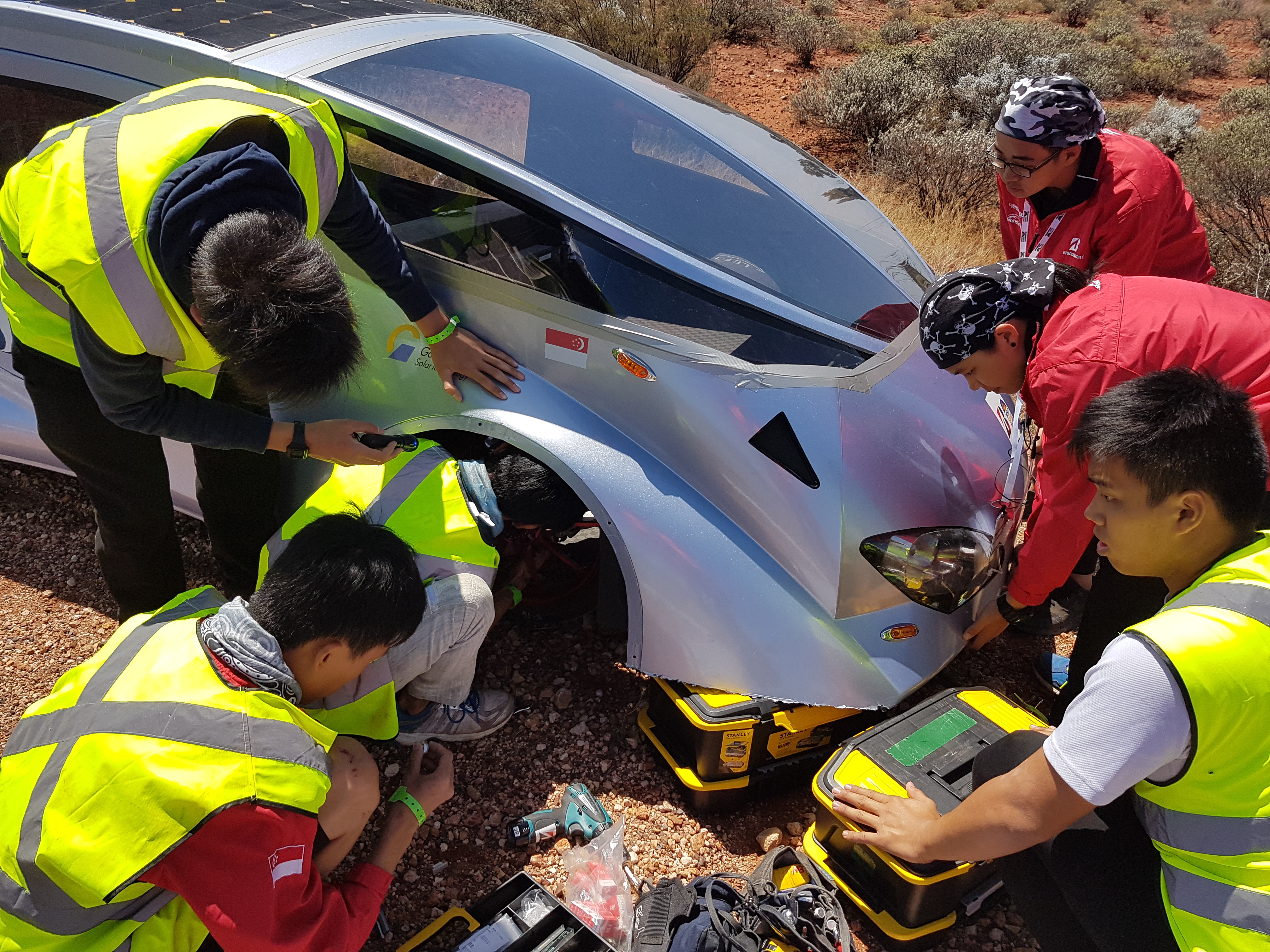Fixing a tire to continue on their grueling 3000km race from Darwin to Adelaide
