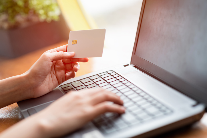 Close up of hand holding credit card and using laptop for online business. shopping or online payment concept.