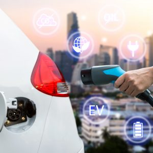 Air pollution and reduce greenhouse gas emissions concept. Hand holding and charging Electric car with blur city view background.