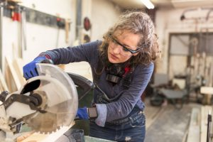 Woman carpenter using circular saw.
