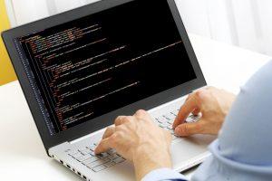 programmer profession - man writing programming code on laptop