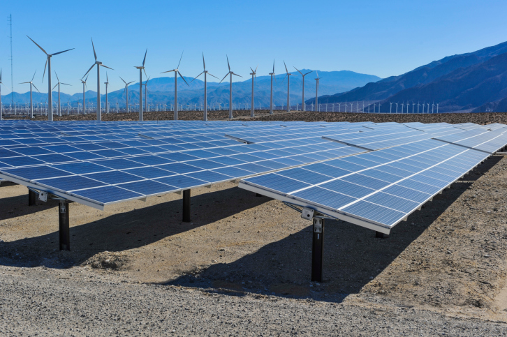 Solar panels in front of wind turbines and mountains